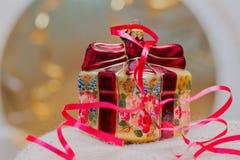 关闭装饰圣诞节装饰在有红色丝带的一个礼物盒在金子被弄脏的背景 选择聚焦 免版税库存图片