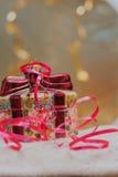 关闭装饰圣诞节装饰在有红色丝带的一个礼物盒在金子被弄脏的背景 选择聚焦 图库摄影