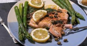 关闭观点的一条烤有机三文鱼用雀跃和莳萝 免版税图库摄影