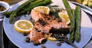 关闭观点的一条烤有机三文鱼用雀跃和莳萝 免版税库存图片