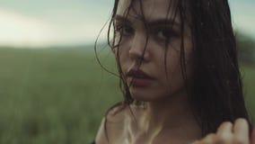 关闭观点的有在雨中浸泡的光秃的肩膀的一个华美的少妇 在美丽的woman's面孔的雨下落 影视素材