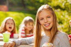 关闭观点的美丽的女孩用杯形蛋糕 免版税图库摄影