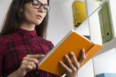 关闭讨厌的女孩读一本科学幻想小说书 库存图片