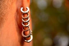 关闭许多在妇女的耳朵的耳环 图库摄影