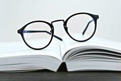 关闭读的行家玻璃在一本开放书 库存照片