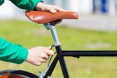 关闭调整固定的齿轮自行车马鞍的人 免版税图库摄影