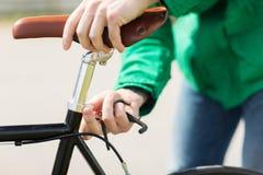 关闭调整固定的齿轮自行车马鞍的人 库存照片
