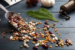关闭豆类的分类在一个不锈的瓢的,溢出在木桌面背景,胡椒研磨机,葱,大蒜和 免版税库存照片