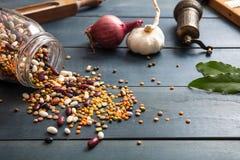 关闭豆类的分类在一个玻璃瓶子的,溢出在一个木桌面背景、胡椒研磨机、葱、大蒜和花格 图库摄影