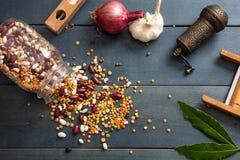 关闭豆类的分类在一个玻璃瓶子的,溢出在一个木桌面背景、胡椒研磨机、葱、大蒜和花格 免版税库存图片