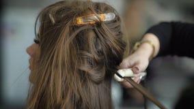 关闭豪华美容院的专家的手在做浅黑肤色的男人的卷曲高发型的过程中 影视素材