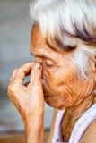 关闭资深亚洲妇女面孔和眼睛,有窦炎窦炎的亚裔资深妇女 库存图片
