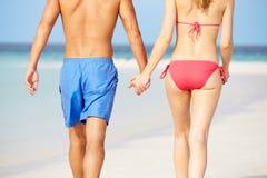 关闭走在热带海滩的浪漫夫妇 免版税库存照片