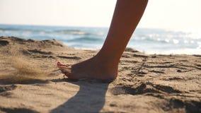 关闭走在金黄沙子的女性脚在与海浪的海滩在背景 年轻女人跨步的腿 股票视频