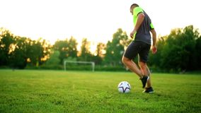 关闭足球运动员的腿和脚穿黑鞋子的行动的运行和滴下与使用的球  影视素材