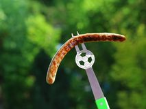 关闭足球迷叉子用在绿色庭院bokeh的串起的烤香肠 免版税库存图片
