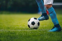 关闭足球选手的腿和脚蓝色运行和滴下与球的袜子和鞋子的 免版税库存照片