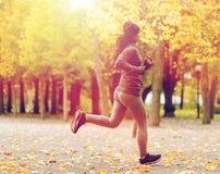 关闭跑在秋天公园的少妇 免版税库存图片