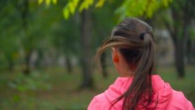 关闭跑通过秋天公园的妇女在日落,后面看法 慢的行动 股票录像