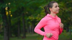 关闭跑通过秋天公园的妇女在日落 慢的行动 股票录像