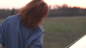 关闭跳舞蓝色牛仔裤夹克的年轻红头发人妇女在日落期间在汽车附近 股票录像