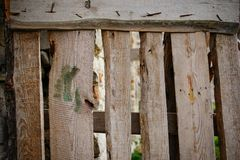 关闭轻的木板条的垂直的篱芭背景钉牢与紧固件并且有在彼此之间的镇压  免版税库存图片