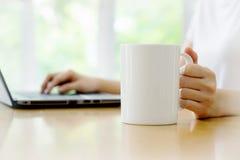 关闭输入在咖啡店te的一台膝上型计算机的妇女手 图库摄影