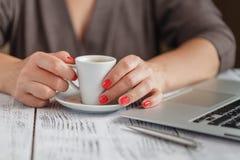 关闭输入在咖啡店te的一台膝上型计算机的妇女手 库存照片