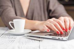 关闭输入在咖啡店te的一台膝上型计算机的妇女手 库存图片