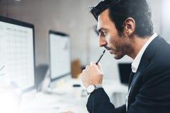 关闭运作在台式计算机上的晴朗的办公室的商人画象,当坐在桌上时 蠢材 免版税图库摄影