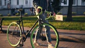 关闭运动鞋的走除一辆自行车以外的妇女英尺长度在早晨公园或街道 年轻人的侧视图 股票视频