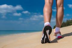 关闭运行在马拉松的海滩训练的赛跑者的脚 免版税库存照片