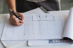 关闭运转在桌,他图画项目剪影在建造场所或办公室上的工程师手 库存照片