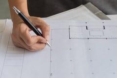 关闭运转在桌,他图画项目剪影在建造场所或办公室上的工程师手 免版税图库摄影