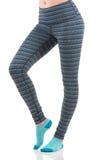 关闭适合做准备在五颜六色的镶边体育绑腿的妇女腿侧视图穿蓝色袜子 免版税库存图片