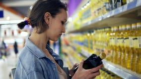 关闭选择产品的妇女在超级市场 读标签在瓶油 放一入推车 分类  影视素材