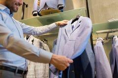 关闭选择夹克的人在服装店 库存照片