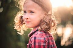 关闭逗人喜爱的微笑的儿童女孩夏天室外画象格子花呢披肩礼服的 免版税库存照片