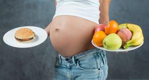 关闭逗人喜爱的怀孕的腹部肚子和健康食物 免版税库存图片
