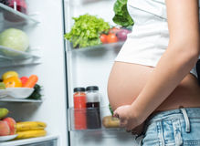关闭逗人喜爱的怀孕的腹部肚子在冰箱附近 图库摄影