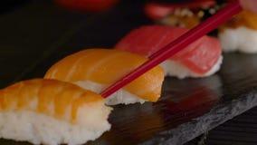 关闭采取寿司卷的部分在桌餐馆的红色筷子 股票视频