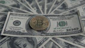 关闭金子在100美元票据的Bitcoin BTC硬币  全世界真正互联网cryptocurrency和数字式 影视素材