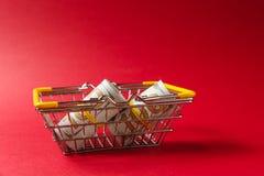 关闭金属购物的杂货篮子在有被降下的黄色把柄的超级市场有捆绑的美元 免版税库存照片