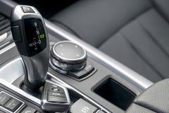 关闭钥匙和自动变速杆在黑皮革内部,汽车内部细节 库存照片