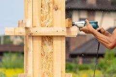 关闭钻子仪器播种的照片在工作者手上 使用工具的他做在木杆建筑或专栏的孔 图库摄影