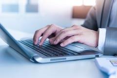 关闭键入在便携式计算机上的商人手 免版税库存照片