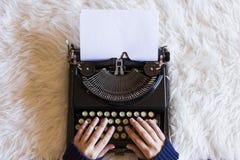 关闭键入在减速火箭的打字机的女性手 杯coff 免版税库存照片
