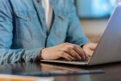 关闭键入在膝上型计算机的男性手 库存照片