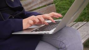 关闭键入在膝上型计算机键盘的撰稿人的手外面在慢动作 影视素材