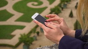 关闭键入由智能手机的女性手有凡尔赛在慢动作的庭院背景 股票录像